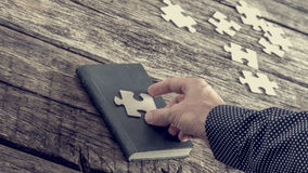 Person placing a jigsaw piece on a book cover Stock Images