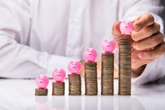 Person Placing Piggybank On Increasing Stacked Coins stock photos