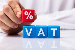 Person Placing Red Percentage Block Over Vat royalty free stock photography