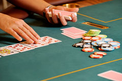 Person playing cards in casino. Hands of person playing cards with chips on green baize casino table with drop hole Stock Photo