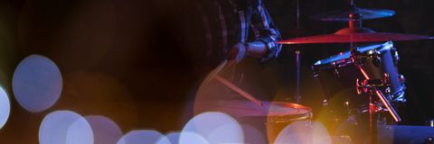 Person playing drums with blue lights Stock Photos
