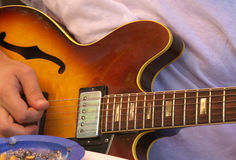 Person playing guitar. Close up of person playing electric guitar, ashtray in foreground Royalty Free Stock Photos
