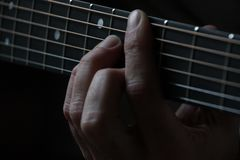 Person Playing Guitar and Holding the Cord Using Left Hand Royalty Free Stock Photography