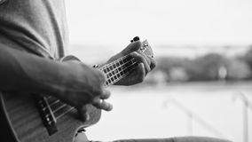 Person playing on little ukulele guitar. Black and white crop shot of man holding and playing on little acoustic ukulele guitar sitting in the outdoor park stock footage