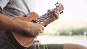 Person playing on little ukulele guitar. Crop shot of man holding and playing on little acoustic ukulele guitar sitting in the outdoor park stock video