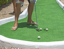 Person playing mini golf putting at the hole Stock Photo