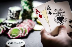 Person playing poker and looking at cards stock images