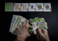 Person playing poker and looking at cards royalty free stock photo