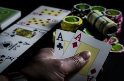 Person playing poker and looking at cards royalty free stock photography