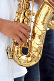 Person playing saxophone. Hand of person playing gold colored saxophone instrument Royalty Free Stock Photos