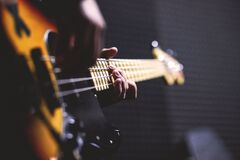 Person Playing Sun Burst Electric Bass Guitar in Bokeh Photography Royalty Free Stock Image