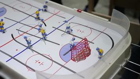 Person playing table ice hockey, hitting puck into opposing net, indoor activity. Stock footage stock video footage