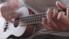Person playing on ukulele guitar inside. Slow dolly crop shot of man holding and playing acoustic ukulele guitar sitting inside stock footage