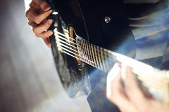 A person plays a black glossy guitar,  while holding a mediator in his hands stock photo