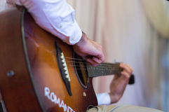 The person plays a guitar, fingers hold a chord. The person plays a guitar Royalty Free Stock Images