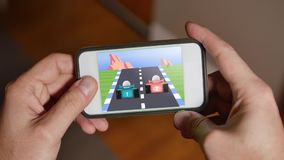 Man Plays Retro 8-Bit Racing Video Game on Smartphone. A person plays a retro 8-bit racing video game on a smartphone stock video footage