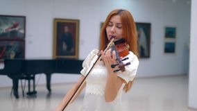 Person plays wooden violin, performs in a museum with pictures. 4K stock footage