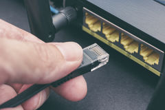 Person plugging in cable to wireless router Stock Photos