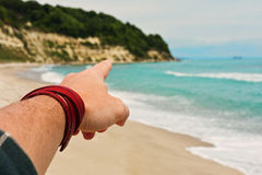 Person pointing direction by finger on a beach Royalty Free Stock Photography