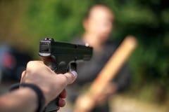 Person pointing a gun at the attacker. Focus on gun. Auto defense concept stock photos