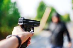 Person pointing a gun at the attacker. Auto defense concept stock image