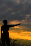 Person pointing at sunset Stock Image