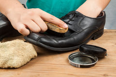 Person polishing and restoring worn out men's formal shoes Stock Photos