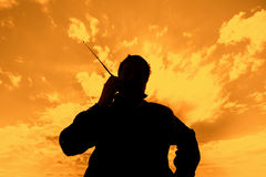 The person with a portable radio set. Silhouette of the man with a portable radio set against the sunset sky Stock Photos