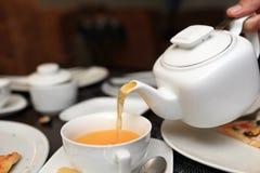 Person pouring buckthorn tea Royalty Free Stock Photos