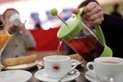 Person pouring fruit tea Royalty Free Stock Photos