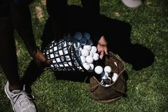 Person Pouring Golf Balls in Brown Leather Bag stock images