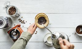 Person Pouring Hot Water in Mug With Ground Coffee royalty free stock images
