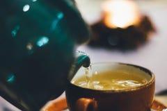 Person Pouring Liquid Into Brown Ceramic Cup Stock Photo