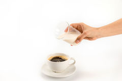 Person pouring milk into cup of fresh hot coffee Royalty Free Stock Image