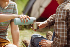 A person pouring tea into his friends cup while camping stock photos