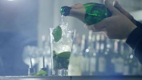 Person pours champagne from bottle into glass with ice and mint leaves on table in bar in easy fog stock footage
