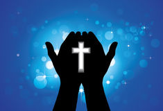 Person praying or worshiping with holy cross in hand. Concept of a devout faithful christian worshiping Jesus Christ with blue background of stars and circles Royalty Free Stock Photos