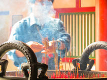 The person prays in the Buddhist temple and lights incense stick Royalty Free Stock Photo