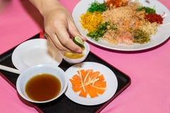 Person preparing Yee Sang or Yusheng Chinese delicacy Stock Photos