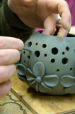 The person processes a clay vase. Cutting of apertures in a clay vase Royalty Free Stock Photography