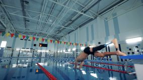 Swimmer with a leg prosthesis jumps into the pool, close up.