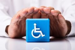 Person Protecting Cubic Block With Disabled Icon stock photos