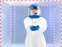 Person in protective suit holding a plant Stock Photos
