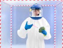 Person in protective suit injecting a vegetable Stock Photos