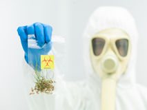 Person in protective suit presenting crop sample Royalty Free Stock Photo