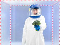 Person in protective suit presenting a vegetable Stock Images