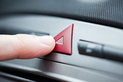 Hazard lights button. Person pushes the hazard lights button Stock Photography