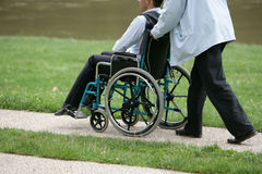 Person pushing a disabled person. In a park Stock Photography