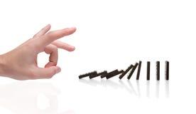 Person pushing domino blocks Stock Images