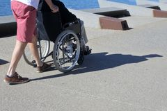 Person pushing a senior adult man on a wheelchair outdoors. Unrecognizable person pushing an unrecognizable senior adult disabled man on a wheelchair outdoors royalty free stock photos